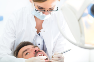 Male patient with female dentist in a dental treatment, wearing