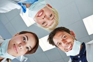 bigstock-Dentist-and-dental-team-lookin-50079350